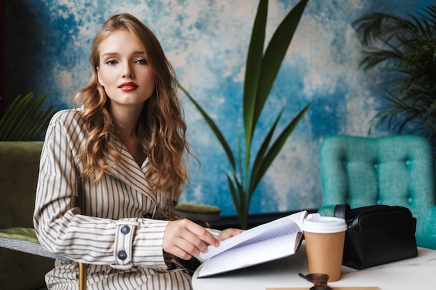 Beautiful girl with wavy hair in striped trench coat sitting with book in hands and coffee to go on table dreamily