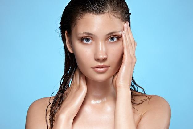 濡れた髪が彼女の顔と首に触れる美しい少女