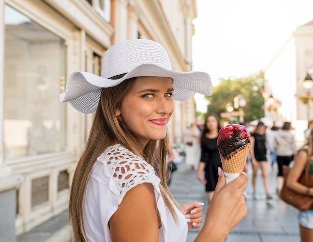 Beautiful girl with white hat and shopping bags eating ice cream on city street