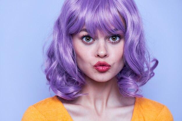 黄色のtシャツと紫の髪のキスをthowingで美しい少女