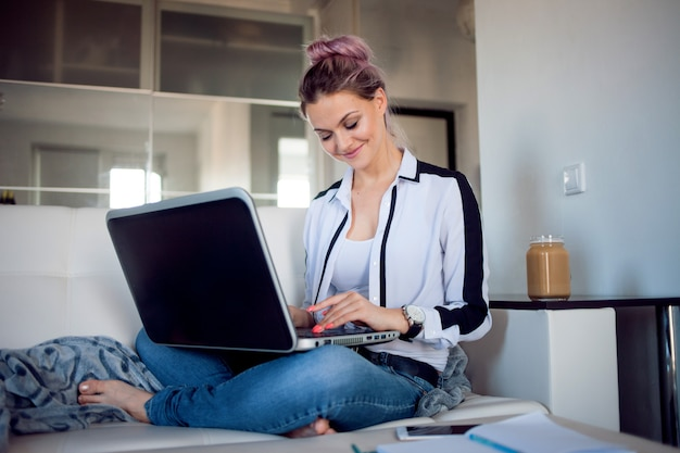Beautiful girl working at home with laptop