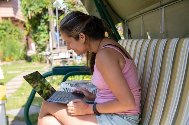 Красивая девушка работает на компьютере в качелях на дистанционном обучении