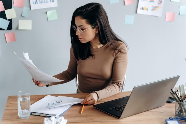 Красивая девушка работает с ноутбуком и документами