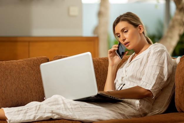 Красивая девушка работает дома за компьютером.