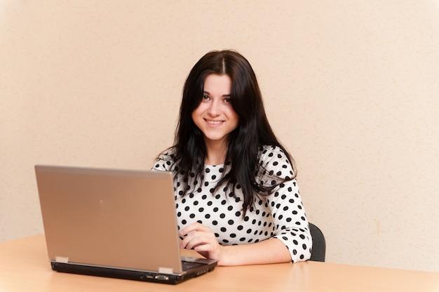 Красивая девушка работает на ноутбуке