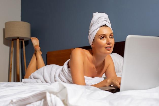 美しい少女はベッドの中でコンピューターで動作します。