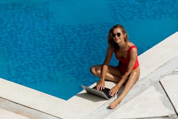 Красивая девушка работает на компьютере возле бассейна