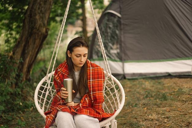 Красивая девушка, завернутая в красный плед, пьет чай в уютном подвесном кресле на открытом воздухе, приключенческое путешествие