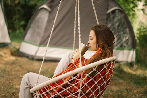 Beautiful girl wrapped in red plaid drinking tea in a cozy hanging chair outdoors adventure travel