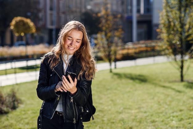晴れた日に通りを歩いている間、スマートフォンでオンラインでメッセージを書いたり読んだりする美しい少女。
