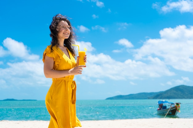 Beautiful girl in a yellow dress drinks fresh mango on the beach of a paradise island. perfect vacation.