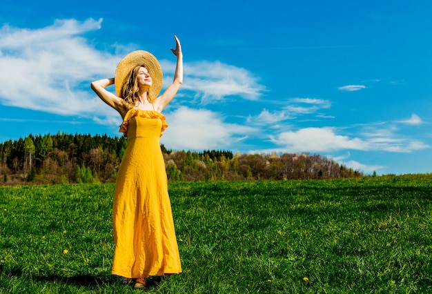 Beautiful girl in yellow dress and on mountain meadow with dandelions.
