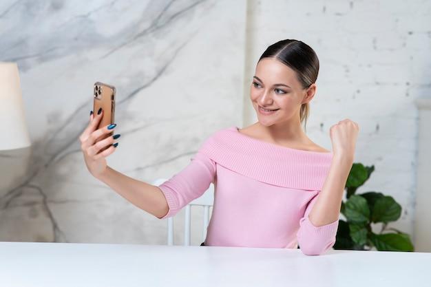 Красивая девушка, молодая счастливая женщина-блоггер смотрит, разговаривает в камеру, транслирует онлайн для видеоблога