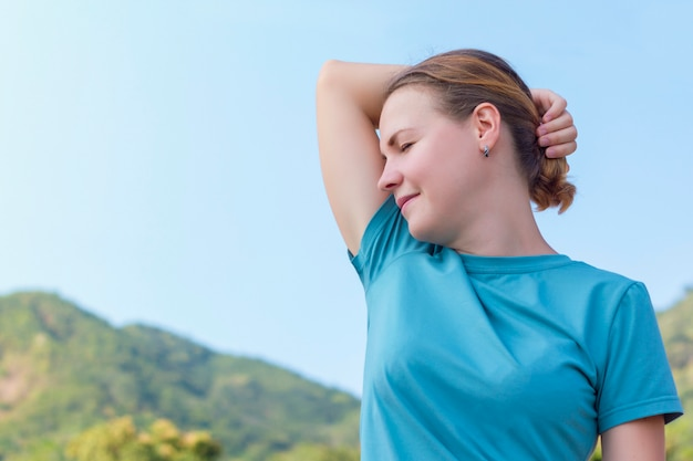 Beautiful girl, young woman sniffing, enjoying the freshness of her clean armpits, smiling. good deodorant, antiperspirant. walk outdoors in the mountains, happy person breathing deep fresh air