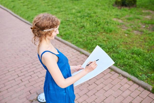 青いドレスを着た通りの美しいgirlartistは絵のスケッチを描きます