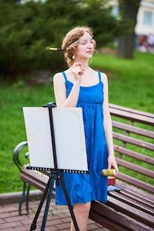 青いドレスを着た通りの美しいgirlartistはイーゼルを描きます