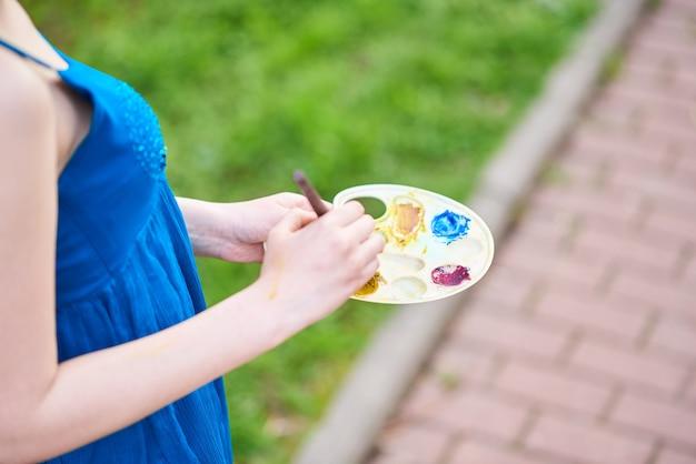 彼女の手でタッセルとパレットで笑っている青いドレスを着た通りの美しいgirlartist
