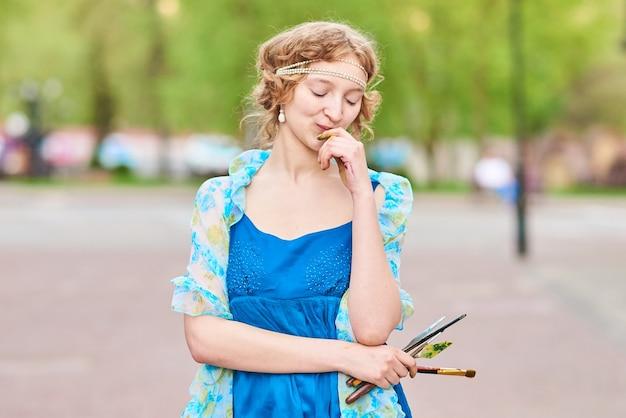 彼女の手でタッセルと笑顔の青いドレスを着た通りの美しいgirlartist