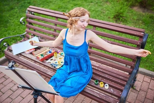 青いドレスを着た通りの美しいgirlartistは彼の手を横に広げます