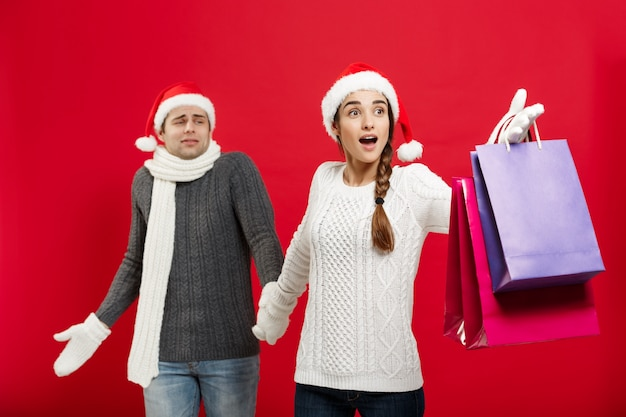 Beautiful girlfriend force her boyfriend to go shopping over red christmas background.