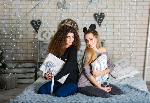 Beautiful girlfriends with gifts for the new year in their hands sit on a blue plaid and smile.