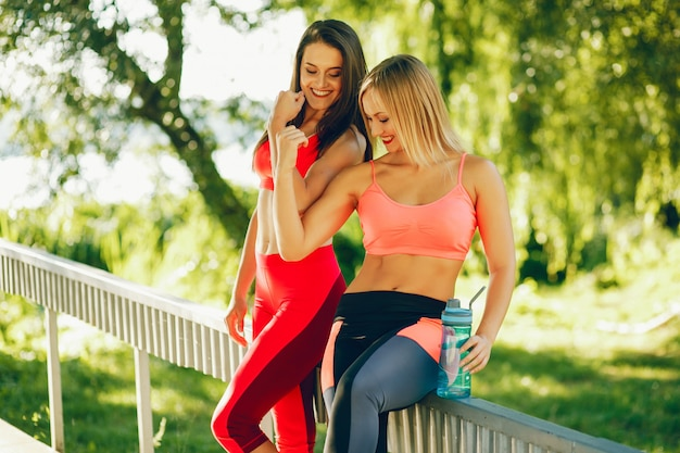 A beautiful girls are engaged in morning exercise in the park.