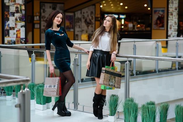 Красивые девушки делают покупки в торговом центре