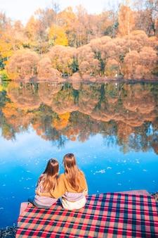 湖の近くの秋の暖かい日に美しい女の子