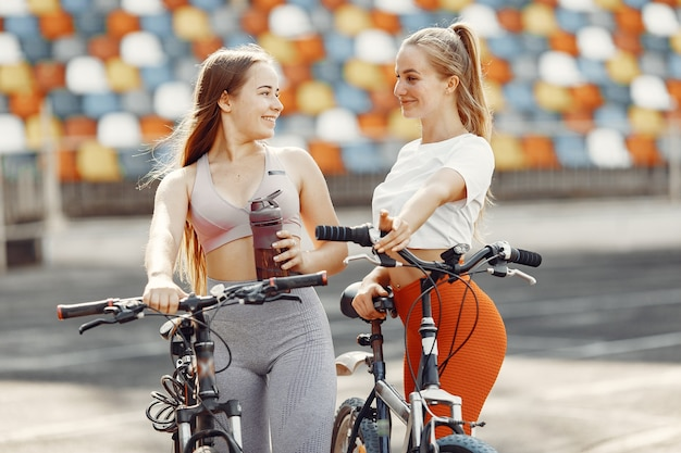 スタジアムの美しい女の子。スポーツウェアのスポーツの女の子。自転車を持っている人。