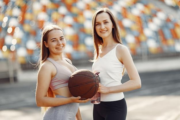 경기장에서 아름다운 소녀. 스포츠웨어의 스포츠 소녀. baskettball 공을 가진 사람들.