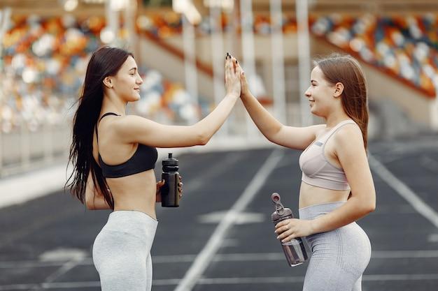 スタジアムの美しい女の子。スポーツウェアのスポーツの女の子。水のボトルを持っている人。
