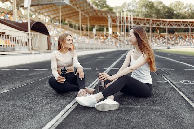 Красивые девушки на стадионе. спортивные девушки в спортивной одежде. люди с бутылкой воды.