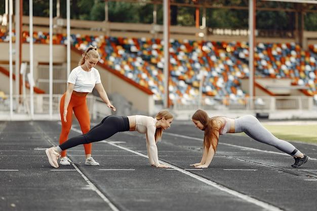 Красивые девушки на стадионе. спортивные девушки в спортивной одежде.