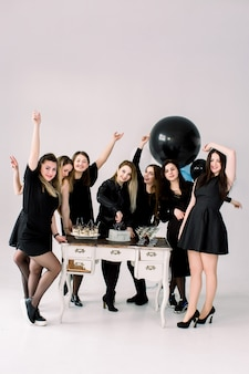 Beautiful girls in black dresses celebrating birthday or hen party, one girl cuts the cake, having fun. decorated table with air balloons, cake, drinks and desserts