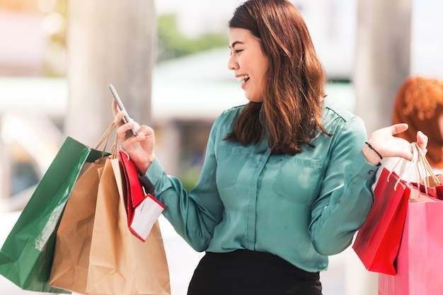 Beautiful girls in city holding shopping bags,using a smart phone playing shopping online