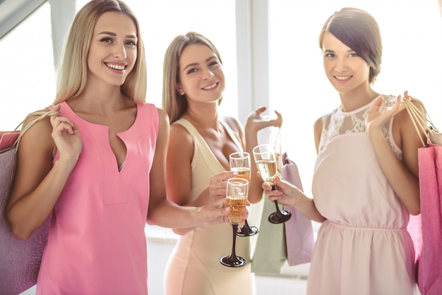 Beautiful girls in cocktail dresses are holding glasses.