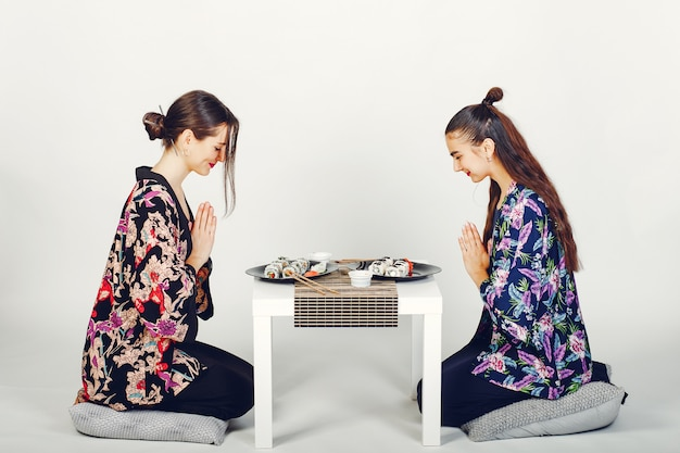 Beautiful girls eating a sushi in a studio