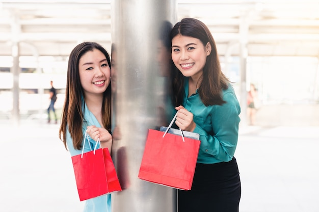 Beautiful girls and friend in city holding shopping bags