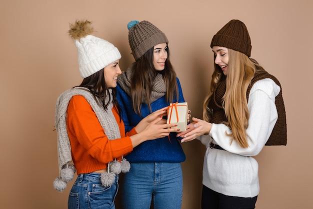 Beautiful girls give a girlfriend a holiday gift
