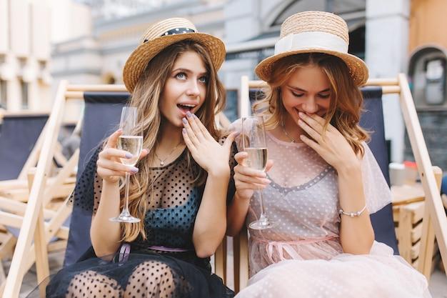 Belle ragazze in stracci allegri che celebrano un evento importante trascorrendo del tempo all'aperto
