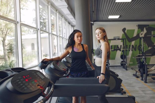 Beautiful girls in a gym. sports ladies in a sportswear. friends in a race track.