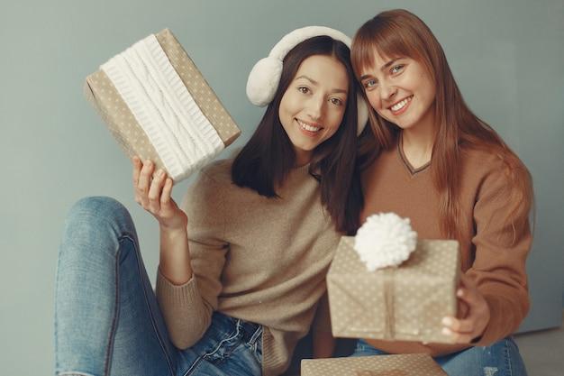 Красивые девушки веселятся в студии с подарками