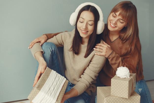 美しい女の子はプレゼントのあるスタジオで楽しんでいます