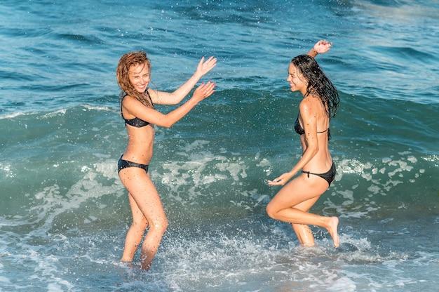 ビーチで楽しんで美しい女の子