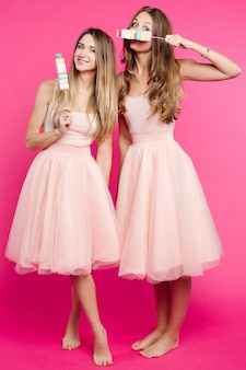 Beautiful girls holding marshmallow candies on stick and hiding face.