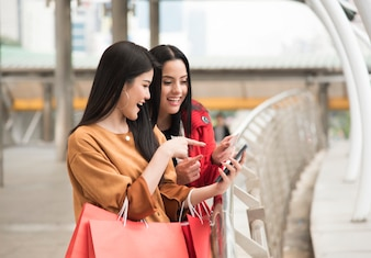 Beautiful girls holding shopping bags using smart phone with credit card