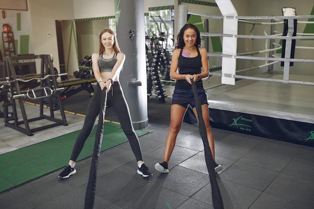 Красивые девушки в тренажерном зале. спортивные дамы в спортивной одежде. тренировка друзей