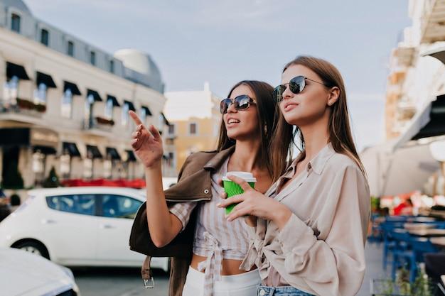태양 안경에 아름다운 소녀는 커피를 들고, 스마트 폰을 사용하고 야외에서 서있는 동안 웃고 있습니다.