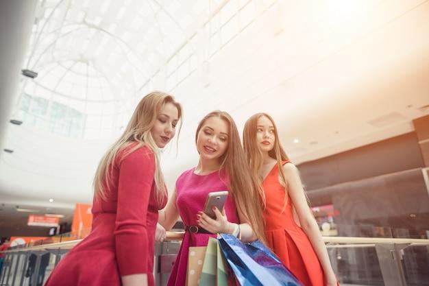 サングラスをかけた美しい女の子が買い物袋を持って、スマートフォンを使って、屋内で立ちながら笑顔