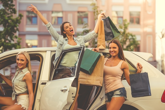 Beautiful girls peeking out of a car with bags